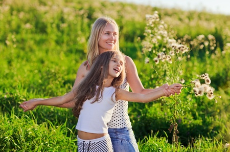 Beautiful mother and daughter family playing on meadow in sunset sun beams photo