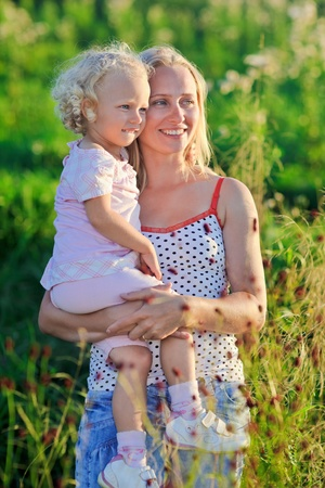 Beautiful mother with infant curly-headed blond daughter on meadow in sunset sun beams Stock Photo - 9287429