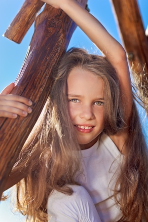 Cute little girl with blond long hair playing on wooden chain swing photo