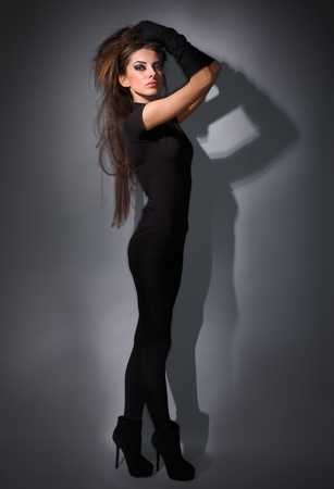 catsuit: Young slim glamour lady with long hairs dressed in black combi dress, dark key studio portrait Stock Photo