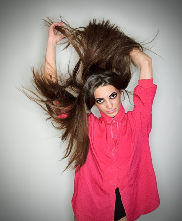 Young brunette lady dressed in pink blouse playing with long hairs, ring flash studio portrait on white photo
