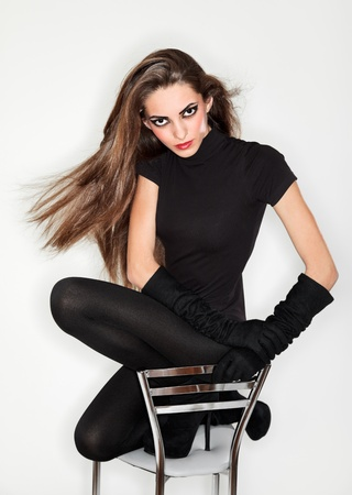 flying hair: Young beautiful woman in black combi dress and velvet gloves, ring flash studio portrait