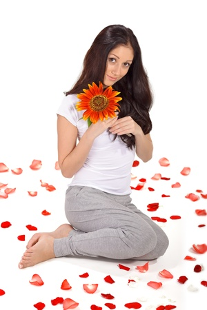Young beautiful woman with sunflower sitting on the floor covered with rose petals Stock Photo - 9345012