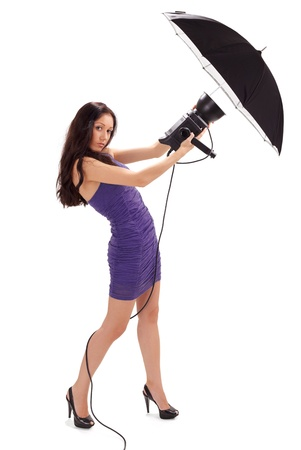 Young pretty lady in blue dress holding studio flash with umbrella isolated on white photo