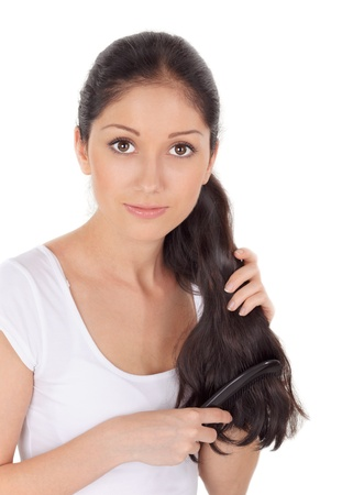 Young brunette beautiful woman combing long hairs on white Stock Photo - 9345015