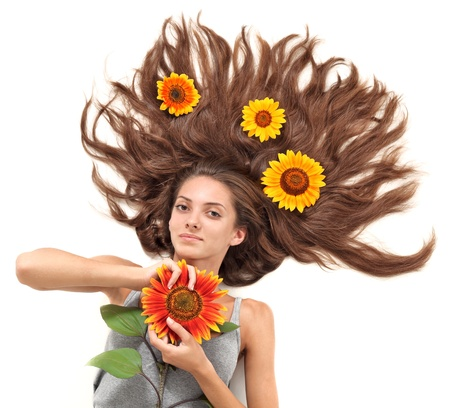 Young beautiful brunette woman with scattered long hairs and sunflower on white Stock Photo - 9345016