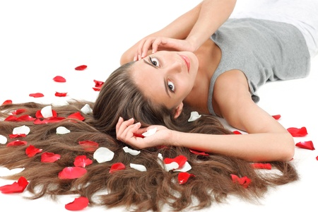 Young beautiful brunette woman with scattered long hairs and rose petals on white photo