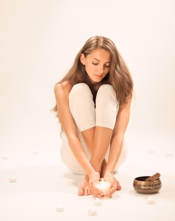 Young beautiful lady relaxing with candle in studio on white photo