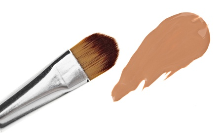 Beige liquid foundation makeup stroke with brush, isolated on white photo
