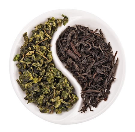 healthy tea: Green leaf tea versus black one in Yin Yang shaped plate, isolated on white Stock Photo