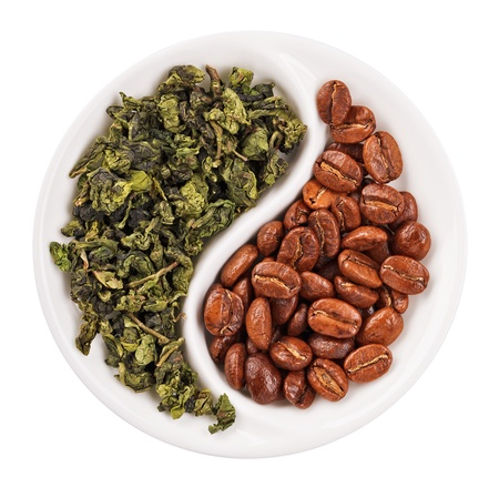 Green leaf tea versus coffee beans in Yin Yang shaped plate, isolated on white photo