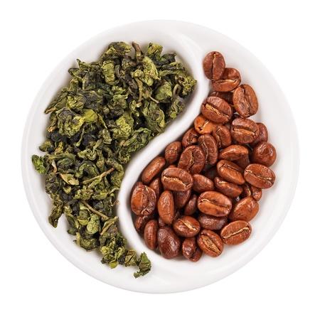 yang yin: T� de hojas verdes frente a los granos de caf� en Yin Yang en forma de placa, aislado en blanco