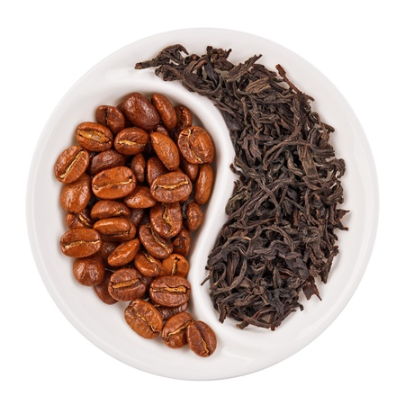 Black leaf tea versus coffee beans in Yin Yang shaped plate, isolated on white photo