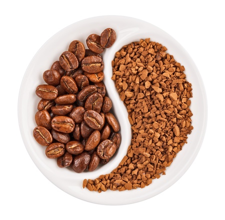 Natural coffee beans versus instant one in Yin Yang shaped plate, isolated on white photo