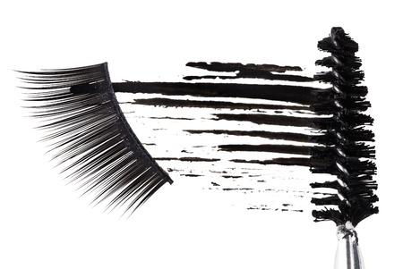 Black mascara stroke, brush and false eyelashes abstract composition, on white photo