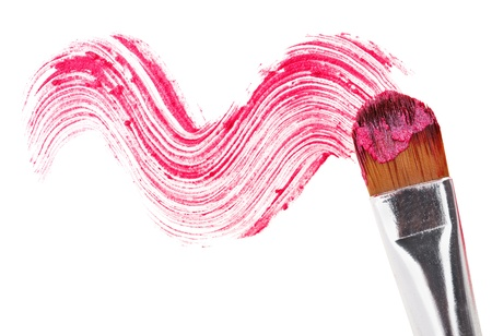 Pink lipstick stroke (sample) with makeup brush, isolated on white photo