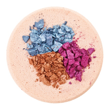 Heap of broken multicolor eyeshadow over makeup sponge, isolated on white macro photo