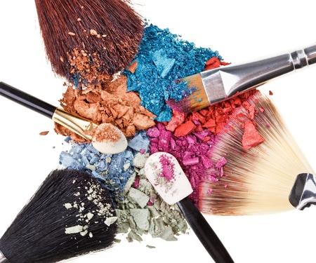 Composición con pinceles de maquillaje y rotas multicolores sombras de ojos