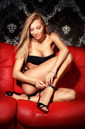 Sexy young blonde lady in black lingerie on red leather sofa Stock Photo - 9783196