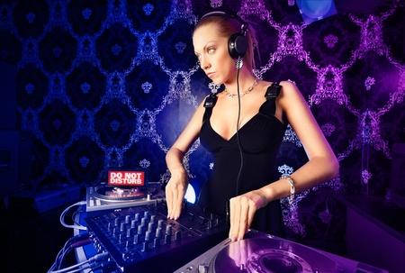 Sexy young blonde lady DJ playing music in night club Stock Photo