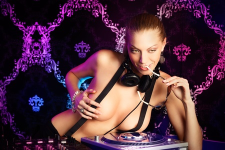Sexy young blonde lady DJ in suspenders at night club photo