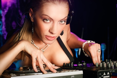 Face portrait of young blonde thoughtful lady DJ at night club photo