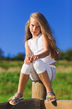 Cute little girl with blond long hair outdoor portrait in front of  blue sky Stock Photo - 9783215