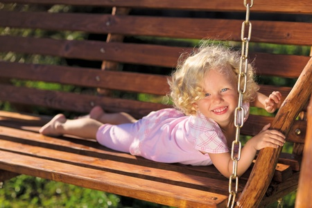 Cute little girl with blond curly hair playing on wooden chain swing photo