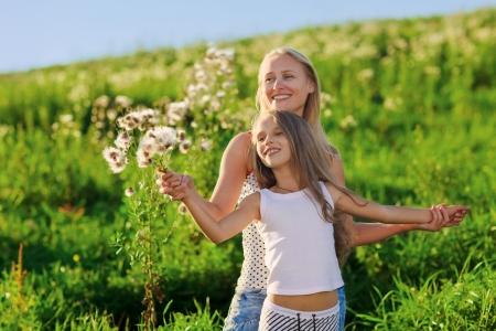 mere et fille: Belle m�re et sa famille fille jouant sur la prairie au coucher de soleil soleil poutres