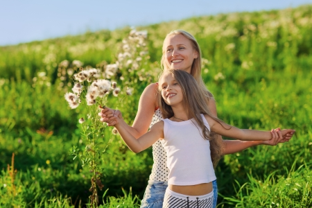 mother and daughter: Hermosa madre y la hija familia jugando en pradera en rayos de sol del atardecer