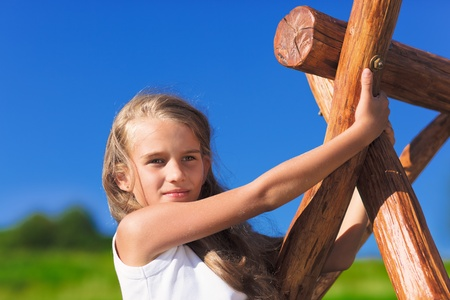 Cute little girl with blond long hair playing on wooden chain swing Stock Photo - 9783221