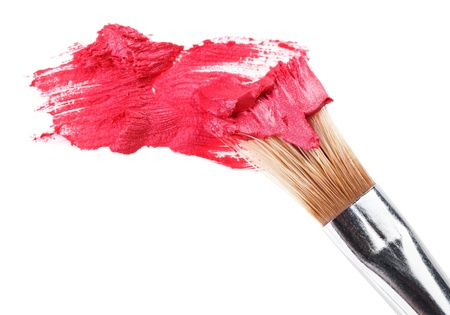Red lipstick stroke (sample) with makeup brush, isolated on white
