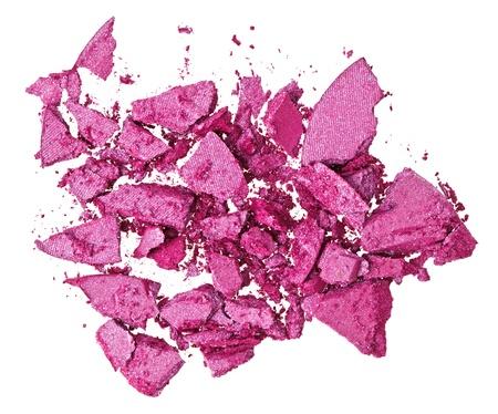 Broken purple eye shadow, isolated on white macro photo