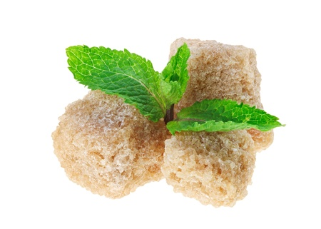 Three brown lump cane sugar cubes with peppermint leaves, isolated on white This shot is made with stacking technology from 11 separate shots with different focus point and has extremely high depth of field and sharpness over all object. photo