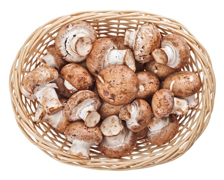 Brown champignon mushrooms in wicker wooden basket, isolated on white photo