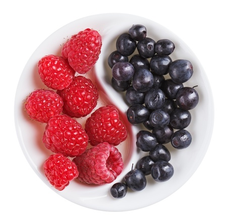 versus: Red raspberry versus black bilberry in Yang Yin shaped plate, isolated on white Stock Photo