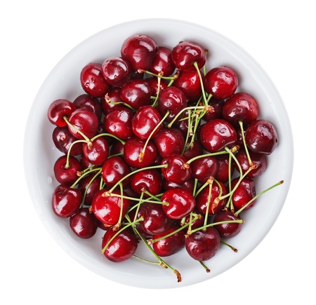 Many red wet cherry fruits (berries) in round plate, isolated on white photo