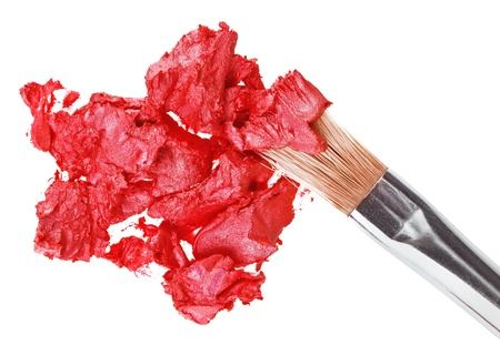 Red lipstick stroke (sample) with makeup brush, isolated on white photo