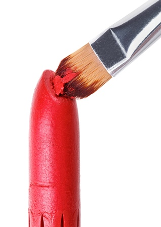 Makeup brush pushed in on red lipstick, isolated on white photo