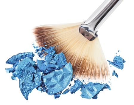 Makeup wide brush with blue crushed eye shadow, isolated on white macro photo