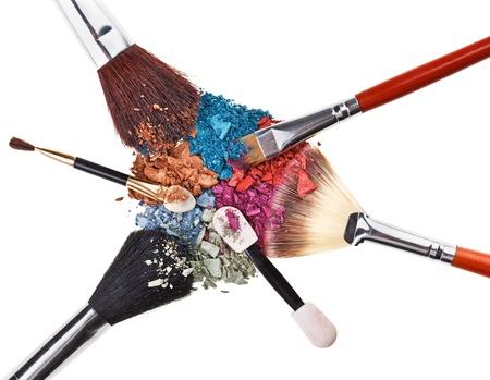 Composición con pinceles de maquillaje y sombras de ojos multicolores rotas