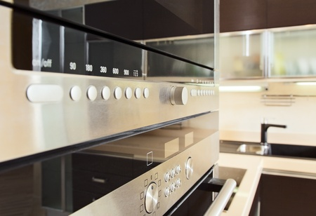 Build in microwave oven in modern kitchen interior with hardwood furniture photo