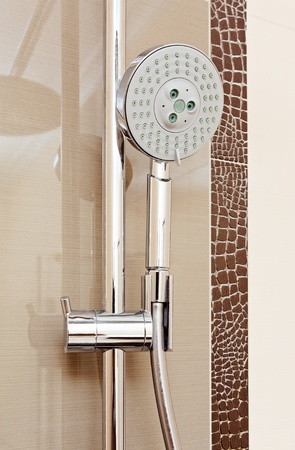 shower cubicle: Metal shower tap in modern bathroom with brown ceramics tile