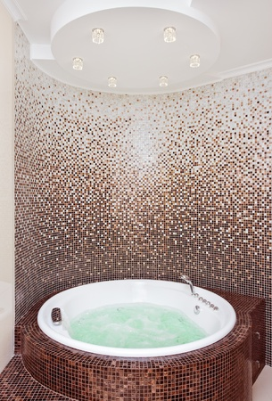 hydromassage: White round jacuzzi in modern bathroom with brown mosaic and counter ceiling
