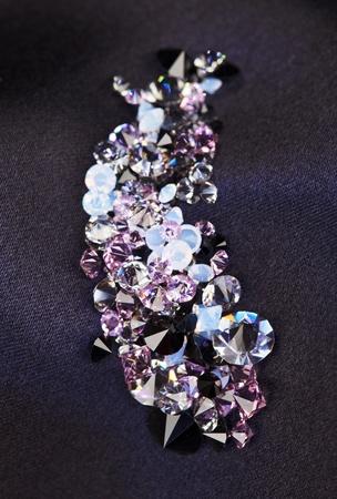 Diamond (small purple jewel) stones heap over black silk cloth background photo