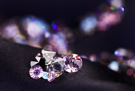 Diamond (small purple jewel) stones heap over black silk cloth background photo