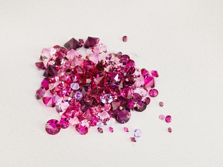 Diamond (ruby) stones heap over cream silk cloth background photo