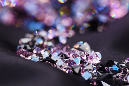 diamond stones: Diamond (small purple jewel) stones heap over black silk cloth background