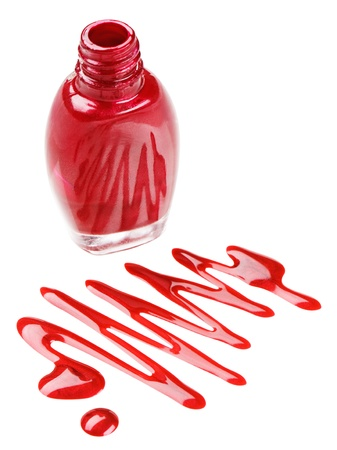 Bottle of red nail polish with enamel drop samples, isolated on white photo