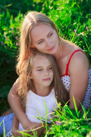 Beautiful mother and daughter sitting on green lush grass meadow in sunset sun beams Stock Photo